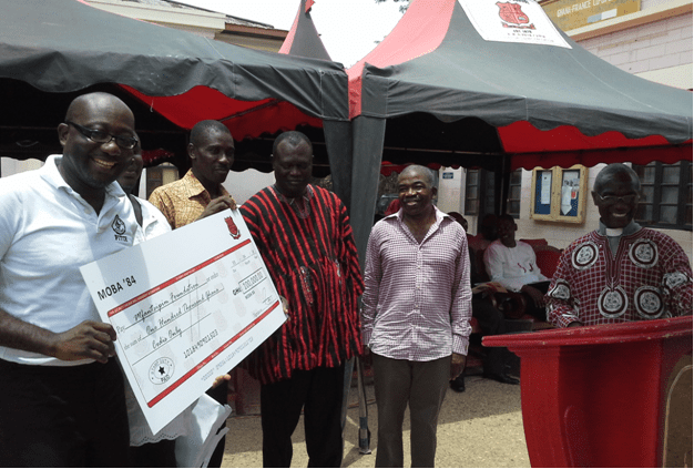 ? Mr. Menser Ben Crentsil, MOBA 1984 (left) with the dummy cheque for GH?100,000.00, whilst (from right) the School Chaplain, Rev. George Affum; Mr. Magnus RexDanquah, Member of the School Board; Mr. J.K.A. Simpson, Headmaster; and Mr. S.K. Yeboah, Assistant Headmaster, Administration.