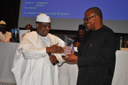 The Speaker of the Federal House of Representatives, Hon. Aminu Tambuwal (left), presenting the Champion 2013 award of