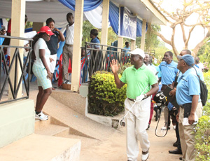 The Asantehene, with a putter, acknowledging cheers from some golfers