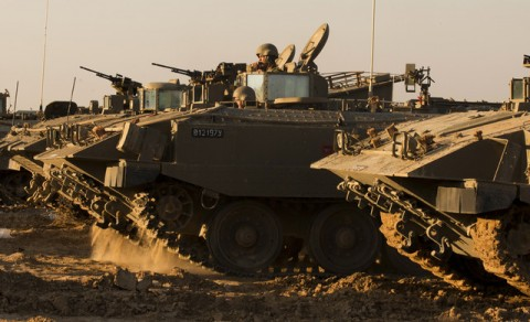 Israeli soldiers rest by their armoured personnel carriers (APC) stationed on the Israel-Gaza border on November 15, 2012.