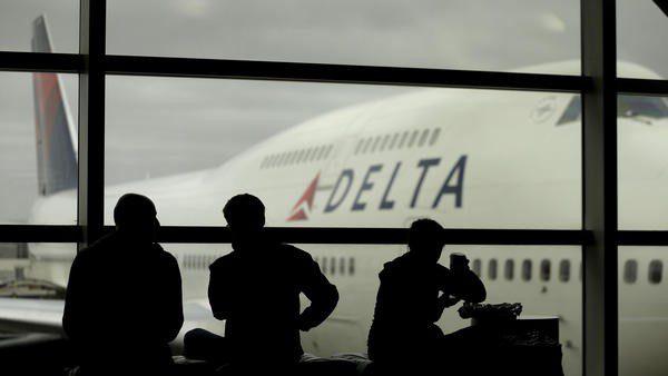 Delta Air Lines passengers wait for flights in Detroit. ?