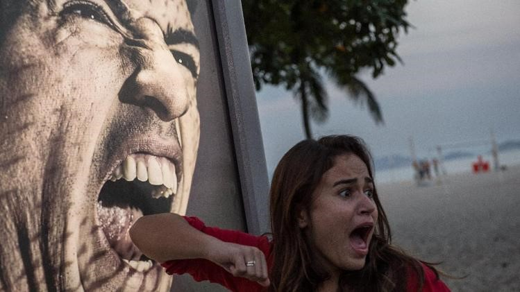 A tourist jokes in front of an advertisement with the portrait of Uruguay's forward Luis Suarez at Copacabana beach in Rio de Janeiro, Brazil ?