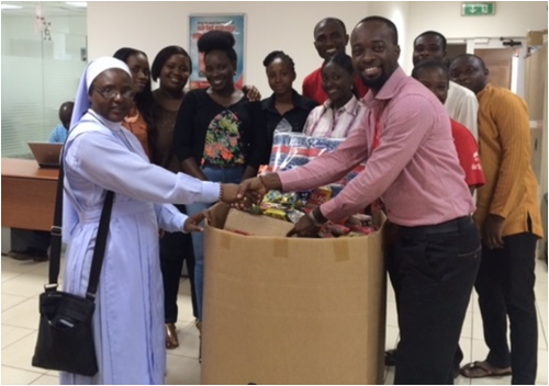 The Trade Marketing Executive at Airtel Ghana presenting the items to Sister Stan.