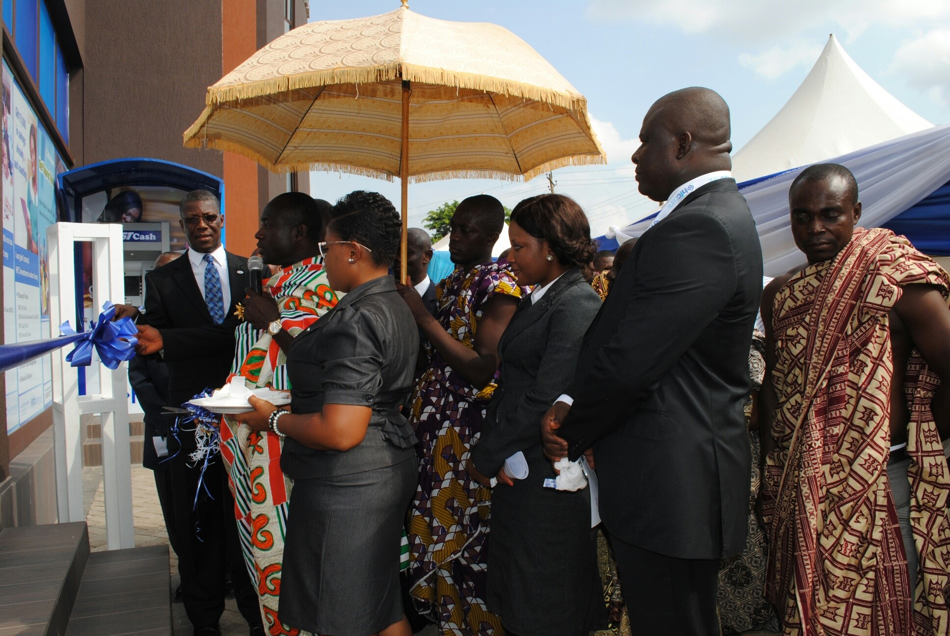 Nana Adu Mensah Asare, Amakomhene, helps Mr Asare Akuffo, MD of??HFC Bank (facing camera) to cut the tape for the inauguration ?