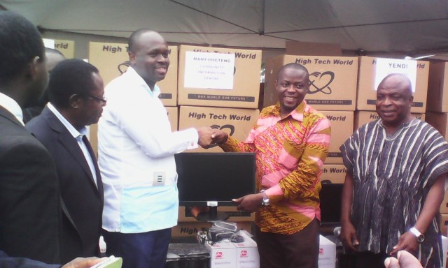 Picture show Dr Omane Boamah, Minister of Communications presenting a computer to one of the managers of the beneficiary CIC?s.