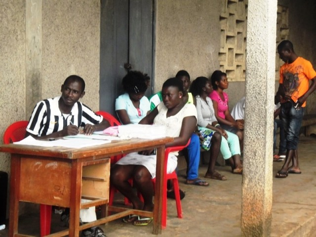 Mr Benedict Clottey (left), Registration Officer at the East Akror Centre attending to people