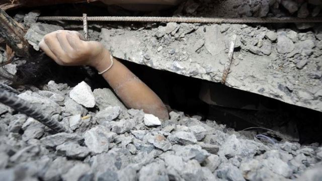 A trapped worker calls for help from the rubble of a collapsed building in Pathumthani province, central Thailand, Monday, Aug. 11, 2014. A six-story building under construction on the outskirts of Thailand's capital collapsed Monday, killing a number of workers and trapping several others underneath the rubble, police said. (AP Photo) THAILAND OUTThe Associated Press