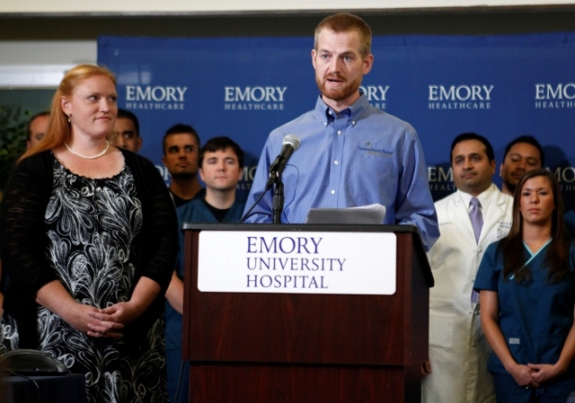 (PHOTO: REUTERS/TAMI CHAPPELL) Dr. Kent Brantly (R), who contracted the deadly virus Ebola, speaks as his wife Amber looks on during a press conference at Emory University Hospital in Atlanta, Georgia, Aug. 21, 2014. The American doctor along with a second American aid worker who contracted Ebola treating victims of the deadly virus in Liberia have recovered and were discharged by the Atlanta hospital that treated them with an experimental drug.