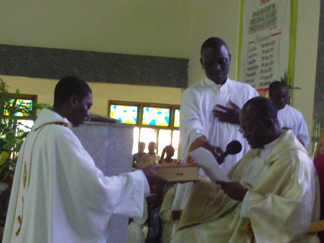 Very Reverend Father Anthony Opong, (kneeling) swearing the oaths before the Very Reverend Father Francis Adoboli, Vicar General (seated), lookin on is one of the Altar Boys.