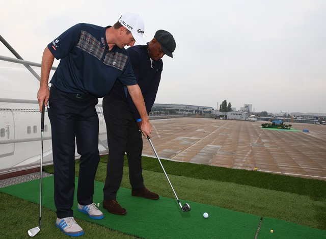 Golfer Justin Rose coaches Ian Wright to play a shot from the wing of a British Airways Boeing 747