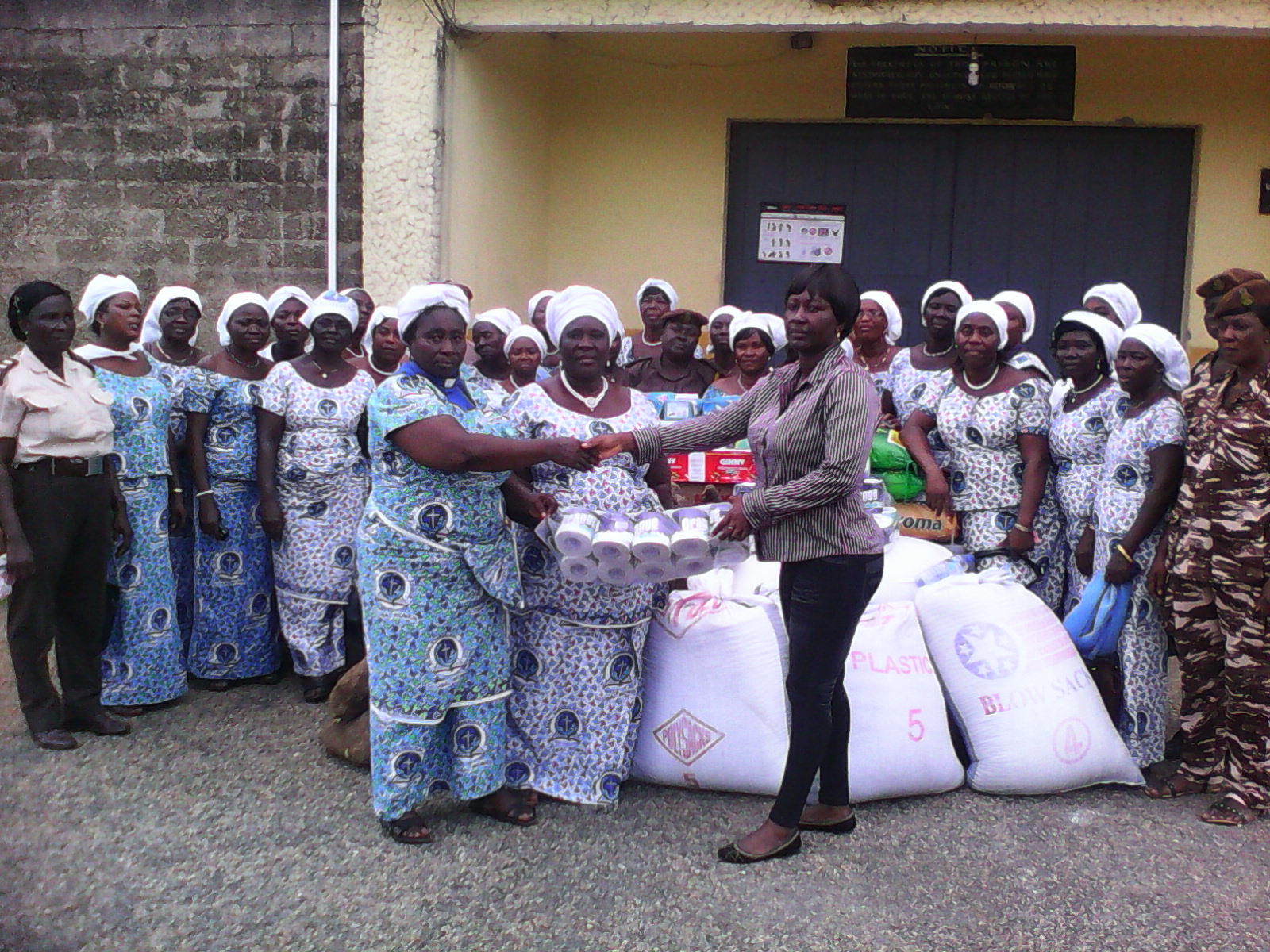 Rev. Edith Adoblosu-Kuhlor in clerical and Mrs Euphemia Gifty Agbavitor jointly presenting the items to ASP Judith Okyere while some members of the church and prison officers look on