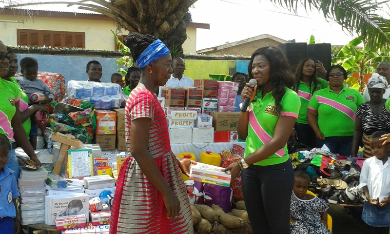 Ms Doe Agbolosoo-Mensah, President of PELA, presenting the items to Madam Evelyn Ansah Appiah, Founder of the Home, while some of the ladies, children and staff looked on.