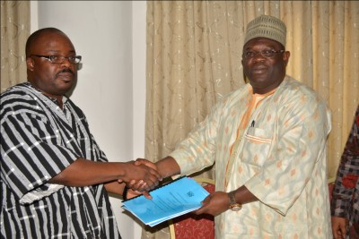 Alhaji Limuna, Northern Regional Minister presenting a copy of the signed contract to Dr Callistus Mahama, Head of Local Government Service in smock