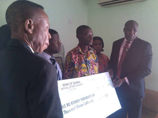 Mr Fiifi Amissah, Manager in charge of Special Projects at National Lottery Authority presenting the dummy cheque to Nicholas Ofosuhene, the kidney patient