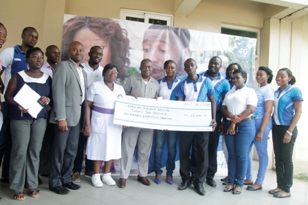 Mr. Kombian Kambarim, Deputy Director of Administration at the Korle Bu Teaching Hospital displaying the cheque while others look on