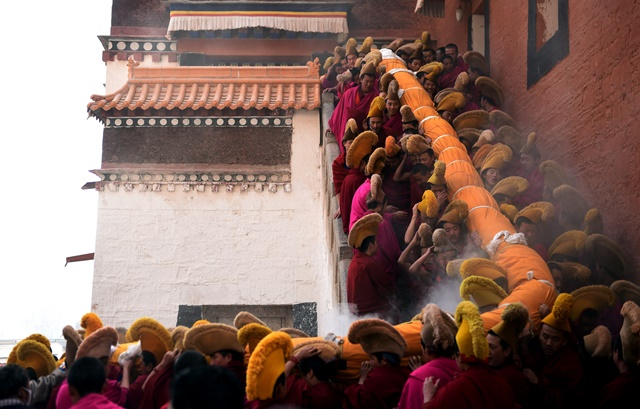 """Lamas carry a gigantic Buddha tangka (Tibetan religious painting) to a hillside for a display, or """"basking of Buddha"""", at the Labrang Monastery in Xiahe County, northwest China's Gansu Province, March 3, 2015. (Xinhua/Fan Peishen)"""