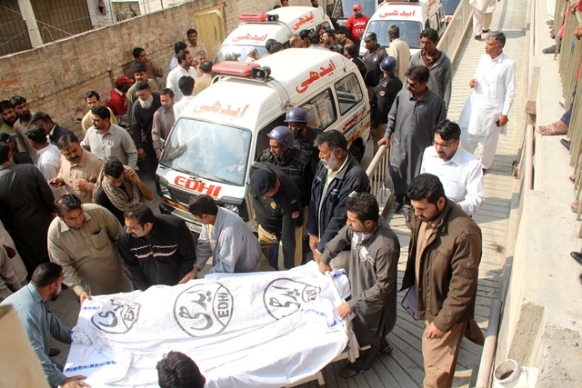 Rescuers transfer the body of a victim to a hospital following suicide bomb attacks on churches in eastern Pakistan's Lahore on March 15, 2015. At least 14 people were killed and 78 others wounded when two suicide bombers blew themselves up at the entrance of churches in Pakistan's east city of Lahore on Sunday, hospital sources said. (Xinhua/Jamil Ahmed)