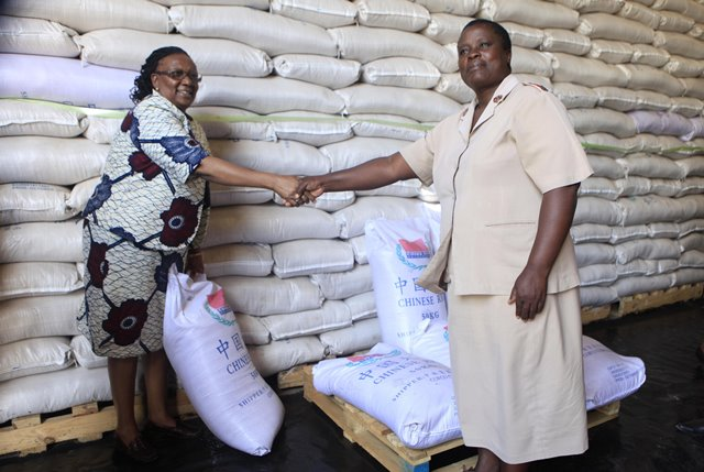 Zimbabwean Public Service, Labor and Social Welfare Minister Prisca Mupfumira (L) hands over China-donated rice to Major Chrisia Nyarudero of Bumhudzo Senior Nursing Home at Grain Marketing Board of Zimbabwe in Harare, Zimbabwe, March 16, 2015. Zimbabwe on Monday received 5,400 metric tonnes of rice worth more than 8 million U.S. dollars from China to help alleviate food shortages in the country. (Xinhua/Stringer)