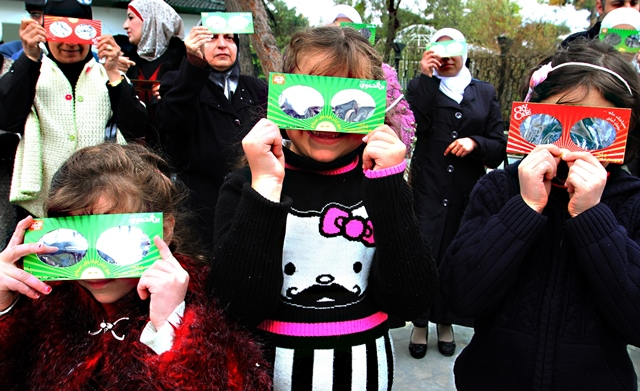 Syrians children observe the partial solar eclipse in Damascus, Syria, March 20, 2015. (Xinhua/Bassem Tellawi)
