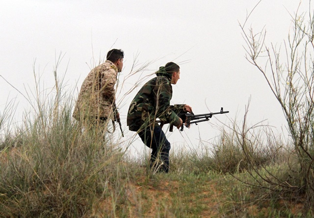 Two Libya Dawn fighters identify positions of their rivals near Bir al-Ghanam, Libya, on March 21, 2015. Clashes continued between Libya Dawn fighters and pro-government forces on Saturday near Bir al-Ghanam, some 90 kilometers southwest of the capital Tripoli. (Xinhua/Hamza Turkia)