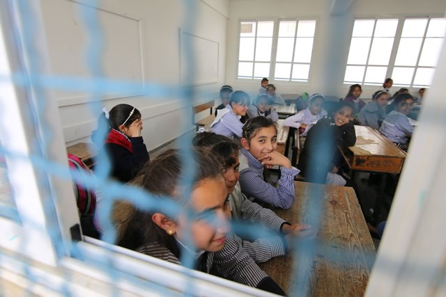 Palestinian students attend a lesson at a UN-run school which is reopened after it was damaged during the war between Israel and Hamas militants in Khuzaa village of the southern Gaza Strip city of Khan Yunis, on March 22, 2015. (Xinhua/Khaled Omar)