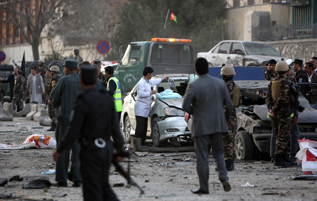 Afghan security forces gather around a destroyed vehicle following a suicide bombing in Kabul, Afghanistan, March 25, 2015. The suicide bombing that rocked Kabul city on Wednesday killed six people and injured 31 others, Kabul Police Chief Abdul Rahman Rahimi said. (Xinhua/Ahmad Massoud)
