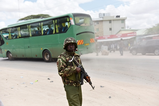 A soldier stands guard while survivor students leave for home in Garissa, Kenya, April 4, 2015. A total of 663 survivors from a Kenyan university attack left Garissa town for their homes Saturday. The survivors, including 50 school staff, were aboard 13 bus. They were departing after camping for two days. (Xinhua/Sun Ruibo)