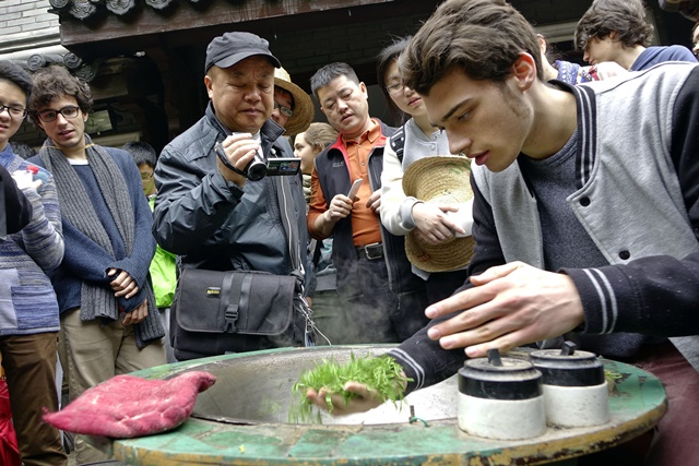 A student from Switzerland tries frying tea with hands as they visit a tea garden in Hangzhou, capital of east China's Zhejiang Province, April 5, 2015. A group of Swiss senior high school students visited a tea garden in Hangzhou with their Chinese peers to learn about the Longjing Tea culture. (Xinhua/Li Zhong) (wyo)