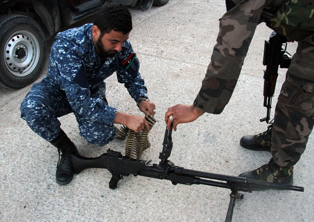 Some Libya Dawn fighters check their weapons before entering the combat zone in al-Azizia, Libya, on April 5, 2015. Clashes continued in al-Azizia on Sunday between pro-government forces and the Islamist armed coalition Libya Dawn. (Xinhua/Hamza Turkia)