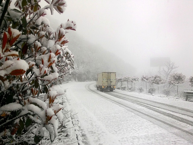A van runs on the road covered with snow in Tang'erhe Village, Baokang County, central China's Hubei Province, April 7, 2015. A cold front brought snowfall to Baokang County on Tuesday. (Xinhua/Yang Tao) (ytt)