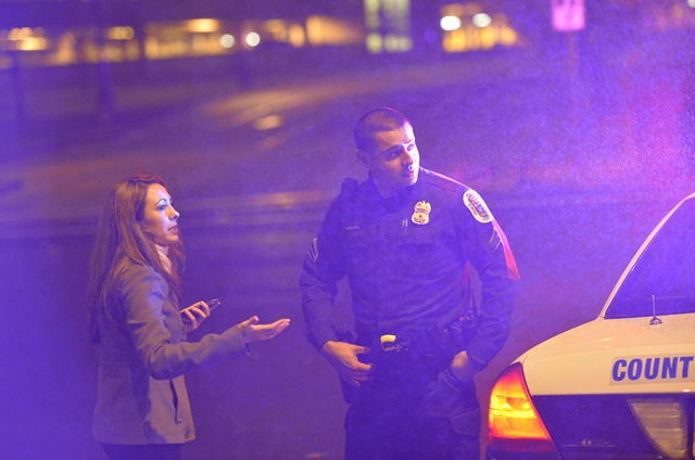 A journalist talks to a policeman at the street beside the U.S. Census Bureau headquarters after shooting happened at the bureau in Suitland, Maryland, the United States, April 9, 2015. A guard at the U.S. Census Bureau headquarters was shot and critically wounded Thursday, local media reported. (Xinhua/Yin Bogu)