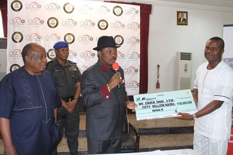 Governor of Anambra State, Chief Willie Obiano presenting a cheque of N50million to a direct beneficiary Mr. Aka Egwuonwu of De Zara Industries Limited with the Chairman of ASBA Board, Hon Greg Obi (First Right) at the Flag-Off of MSMEDF N2bn Fund at Governor?s Lodge Amawbia Wednesday?