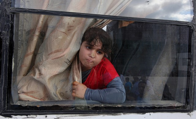 A Palestinian girl looks out from a bus window as she waits with her family to cross into Egypt, at the Rafah border crossing between Egypt and the southern Gaza Strip, June 13, 2015. Egyptian authorities opened the Rafah border crossing on Saturday for three days, in both directions to allow entry and exit of Gazan patients and students, for the first time since March 11, Palestinian officials said. (Xinhua/Khaled Omar) (zjy)