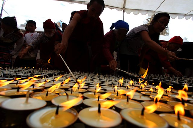 People light butter lamps during a spiritual prayer event to mark the 49th day of the devastating earthquake on April 25 at Boudhanath Stupa in Kathmandu, Nepal, June 13, 2015. During the occasion, 100,000 butter lamps were lit, followed by silent observation and spiritual prayers. (Xinhua/Sunil Sharma) (zjy)