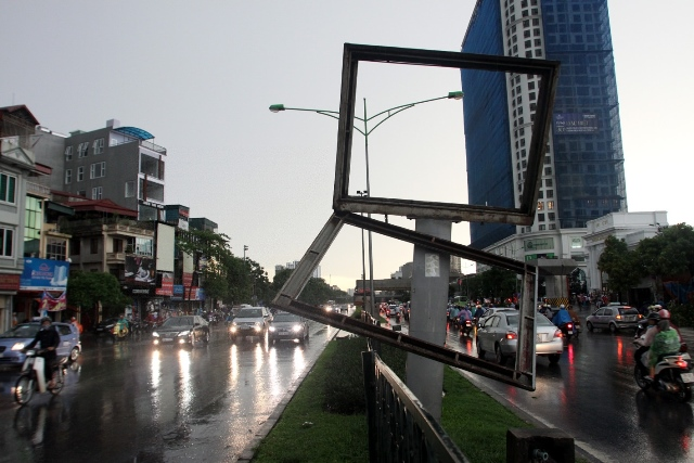 Photo taken on June 13, 2015 shows an advertisement board blown off during heavy rain with strong wind in Hanoi, capital of Vietnam. One person was killed by uprooted tree while three others were wounded. (Xinhua/VNA) (lrz)