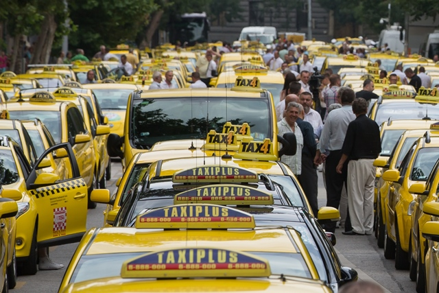 Taxi drivers take part in a demonstration in central Budapest, Hungary, on June 16, 2015. Hundreds of taxi drivers turned up in their yellow cabs at a demonstration against unregulated car-sharing apps such as Uber, demanding the government to carry out a solution. (Xinhua/Attila Volgyi)