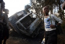 Residents of Kayole Estate walk past a truck that was burnt by irate youth with claims that it was transporting illicit brew in Nairobi, Kenya on July 3, 2015. Kenyan President Uhuru Kenyatta this week revoked the licences of bars and other outlets selling second generation brews in Central region and gave Members of Parliament from Central region of Kenya four days to rid the region of illicit brews..The brew has seen several people die after taking it. (Xinhua/John Okoyo)