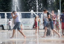 Boys cool off from the heat in fountains on Nations Square in Geneva, Switzerland, July 4, 2015. The World Meteorological Organization (WMO) on Friday warned many parts of Europe will see high or extremely high heat in the coming days. (Xinhua/Xu Jinquan)