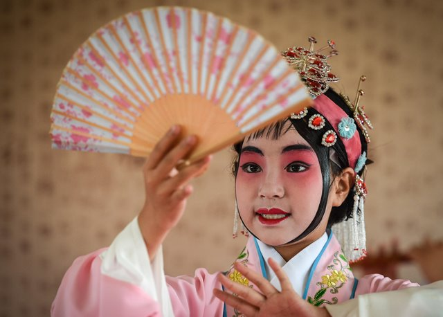 Yang You perform Kunqu Opera in Kunshan, east China's Jiangsu Province, June 26, 2015. The 11-year-old girl Yang You lost her mother when she was six and her father passed away two years later. The misery turns her into a timid and introverted girl. However, she fell in love with Kunqu Opera, a traditional Chinese performing art with a history of 600 years, by chance and became confident and more outgoing. She won a gold medal at a national children's opera competition and kept on chasing her dream of being a professional artist of Kunqu Opera. (Xinhua/Yang Lei)