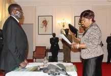 Zimbabwean President Robert Mugabe (L) swears in the new Minister of Women Affairs Nyasha Chikwinya at State House, in Harare, Zimbabwe, on July 6, 2015. The Zimbabwean veteran leader on Monday reshuffled his cabinet for the second time in barely six months. (Xinhua/Stringer)