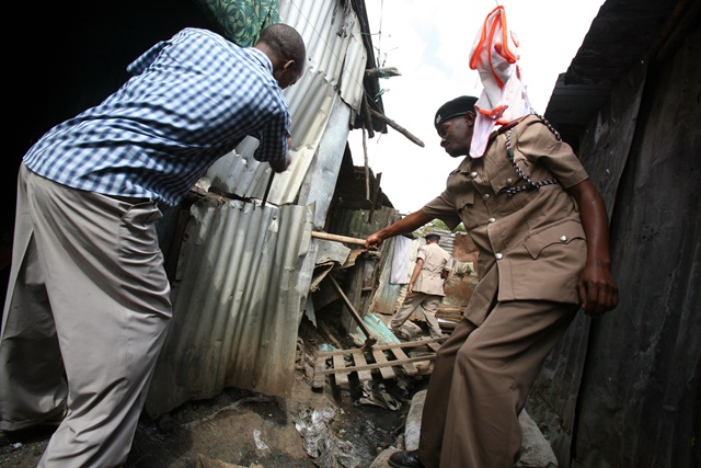 A chief (R) destroys a den during a crackdown on illicit brew at Motherland slums in Nairobi's Eastleigh estate, Kenya, July 14, 2015. Kenyan Interior Cabinet Secretary Joseph Nkaissery on Tuesday said that about 20,000 suspects have been arrested over illicit alcohol and 99 chiefs and sub-chiefs dismissed, and drastic action taken against 15 police officers in the war against the illicit brew. (Xinhua/John Okoyo)