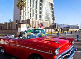 A tourist from California waves a U.S. national flag inside a vintage American car near the U.S. Embassy in Havana, Cuba, on July 20, 2015. Cuba and the United States reopened their respective embassies on July 20 as part of their recent agreement to restore diplomatic relations. (Xinhua/Liu Bin)