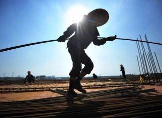 Laborers work at a construction site in Yangzhou, east China's Jiangsu Province, Aug. 3, 2015. The central meteorological authority issued a yellow alert for heat as most parts in China suffered a lingering heat wave. (Xinhua/Meng Delong)