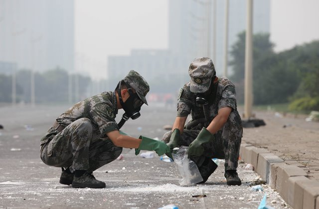 Soldiers of National Nuclear Biochemical Emergency Rescue Team take debris samples near the core area of explosion site in Tianjin, north China, Aug. 15, 2015. A total of 70 specialized anti-chemical soldiers entered the core area of the blasts site on Saturday morning to monitor chemical contamination and search for possible lives. (Xinhua/Wang Haobo) (lfj)