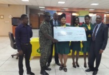 Lt Colonel Yaw Dzotefe Mensah (Rtd), NLA General Manager, Security and Special Projects presenting a dummy cheque to Mr Samuel Ayer, Organising Secretary of the GAA