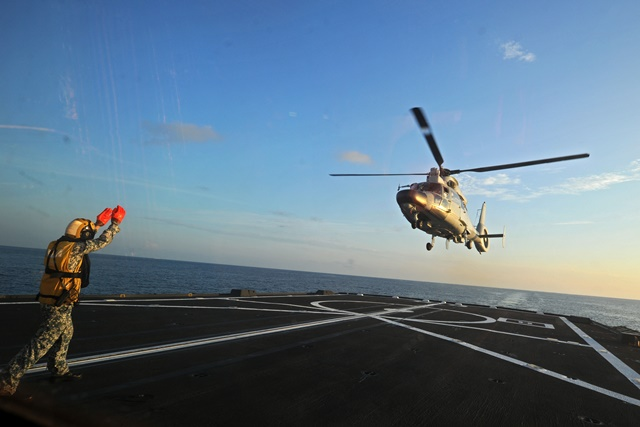 A Dolphin Z-9 helicopter of China's Navy missile frigate CNS Yulin flies off the deck of Singapore's Navy missile frigate RSS Intrepid during the