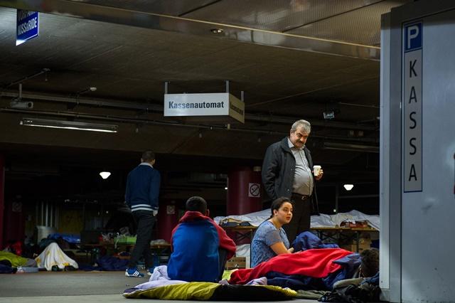 Refugees rest at the parking lot of a railway station in Salzburg, Austria, on Sept. 14. 2015. German Interior Minister Thomas de Maiziere on Sunday announced that Germany temporarily reinstates border control amid the ongoing refugee crisis. According to German newspaper