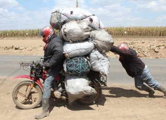 A motorcyclist commonly referred to as 'Boda Boda' in Kenya ferries sacks of charcoal along the Nakuru -Nairobi highway, Nakuru, Kenya, Sept. 16, 2015. Some Kenyan families still use charcoal as the main source of energy consumption due to the high cost of fuel and gas. (Xinhua/Simbi Kusimba)