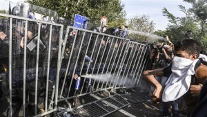 wpid-Hungarian-riot-police-use-pepper-spray-to-push-back-refugees-at-the-Hungarian-border-with-Serbia-near-the-town-of-Horgos-on-September-16-2015-300x169.jpg