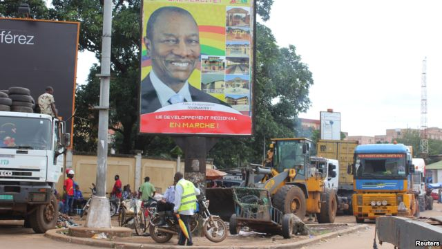 People pass in front of an electoral campaign poster for incumbent President Alpha Conde in Conakry, Guinea, Sept. 10, 2015.